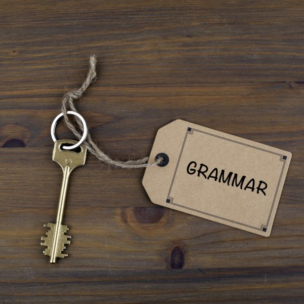 Key and a note on a wooden table with text - Grammar