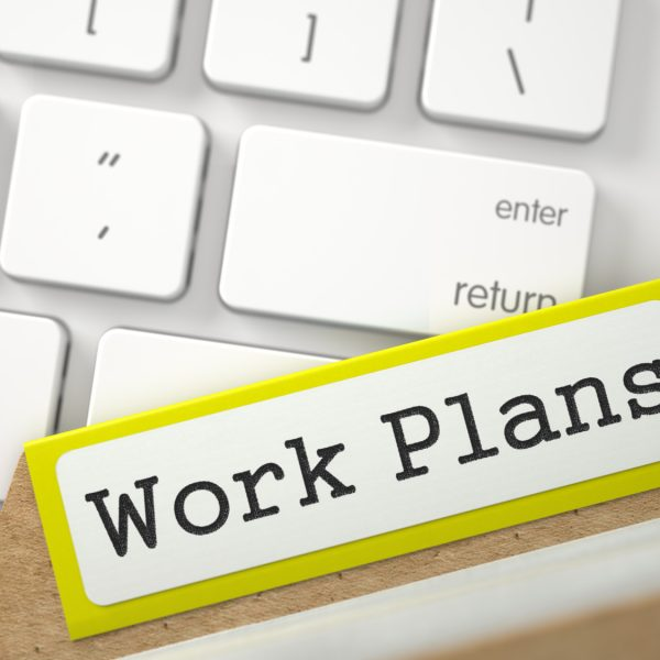 Work Plans written on Yellow Folder Index on Background of White Modern Computer Keyboard. Close Up View. Selective Focus. 3D Rendering.