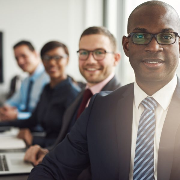 Friendly confident African businessman in a management meeting with a group of multiracial colleagues smiling at the camera
