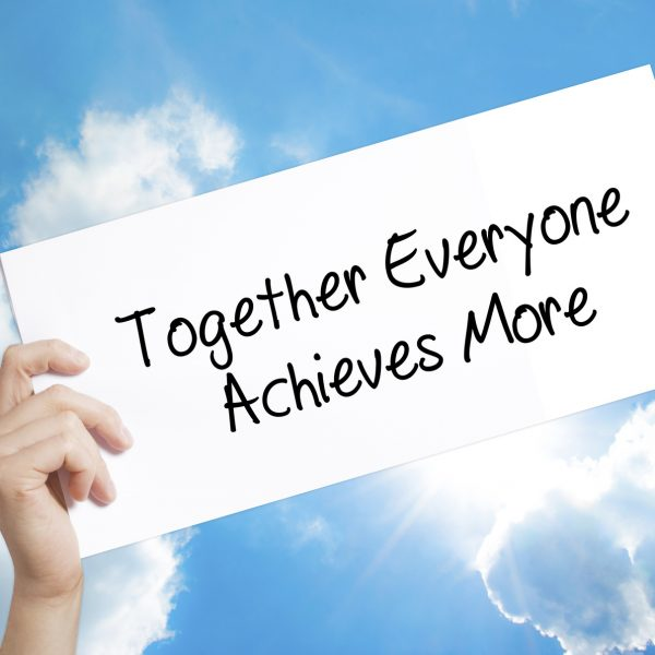 Together Everyone Achieves More Sign on white paper. Man Hand Holding Paper with text. Isolated on sky background.   Business concept. Stock Photo
