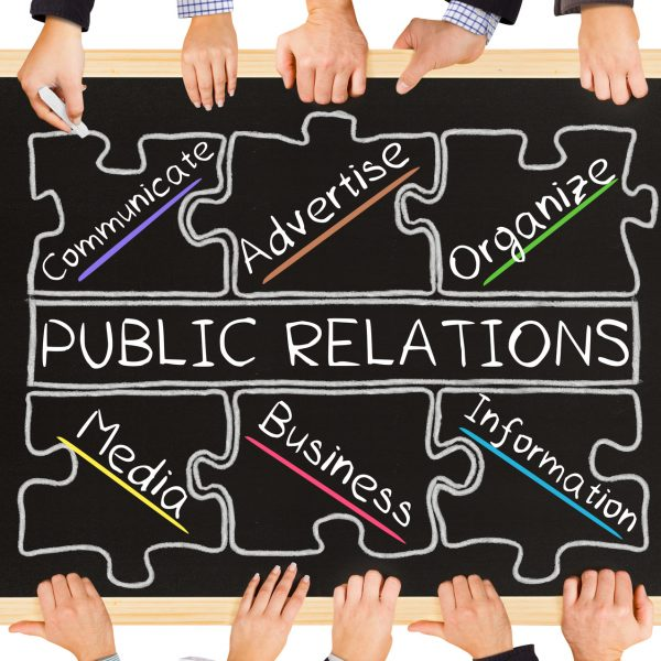Photo of business hands holding blackboard and writing PUBLIC RELATIONS diagram