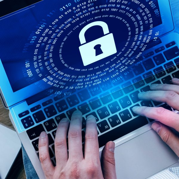 Female hands using laptop with padlock hologram on screen. Privacy concept